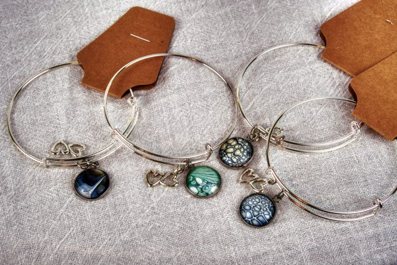 Multiple Bracelets with acrylic pour painting charm and intertwined hearts charm